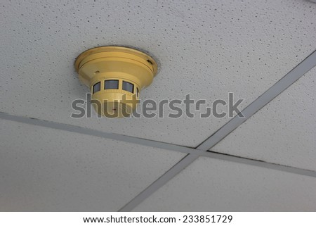 Old smoke detector on ceiling - stock photo