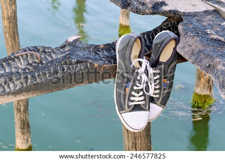Old sneakers hanging on a wooden plank near lake