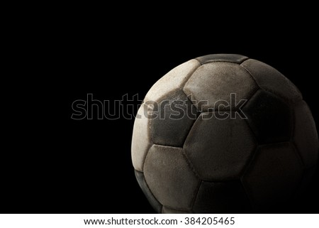 Old Soccer Ball on Black Background / Detail of a old black and white soccer ball on a black background with dark shadows - stock photo