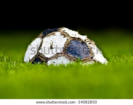 old soccer ball on grass background, end of the game - stock photo