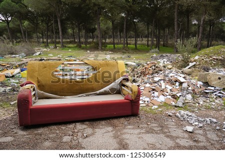 old sofa in a dirty forest - stock photo