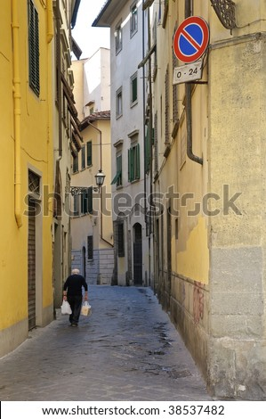 Old solitary man with grocery bags on narrow street - Florence, Italy
