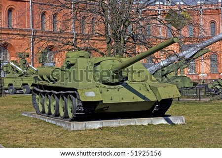 old soviet battle tank near the red building - stock photo