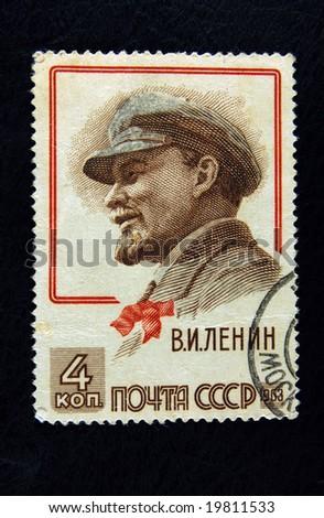 Old Soviet postage stamp with Lenin on black background - stock photo