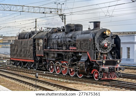 Old soviet steam locomotive series SO arriving at railway station. - stock photo