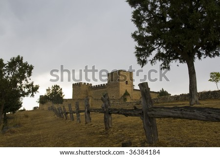 old Spanish castle located in the background behind a wooden fence