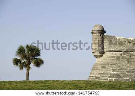 Old Spanish Fort and Palm Tree against a Blue Sky - stock photo