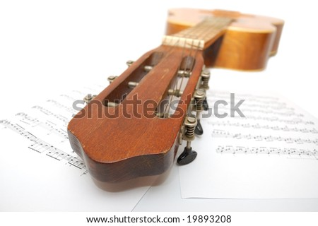 Old Spanish guitar under leaf with notes - stock photo