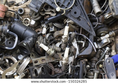 Old spark plug and vehicle parts in repair garage - stock photo