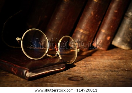 Old spectacles on leather notebook on background with old books - stock photo