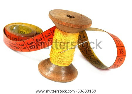 old spool of thread with needle and measuring tape on white background - stock photo