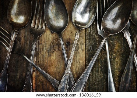 old spoons and forks on a wooden table