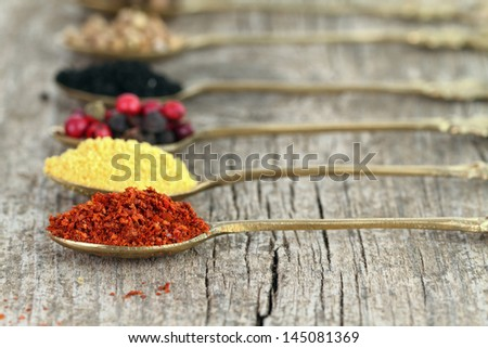 Old spoons with spices on wooden background - stock photo