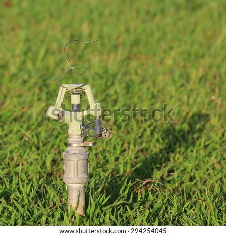 Old sprinkler head in grass field - stock photo