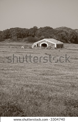 Old stable in a grass field - stock photo