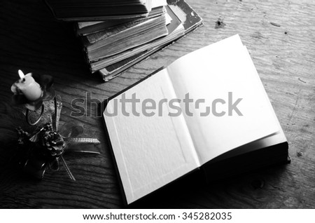 Old stacked book and candle,black and white,horizontal photo - stock photo