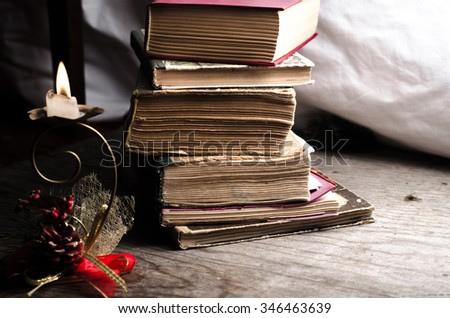 Old stacked book and candle,horizontal photo