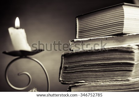 Old stacked book and candle,horizontal photo - stock photo