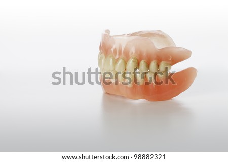 Old Stained Dentures on light grey background.