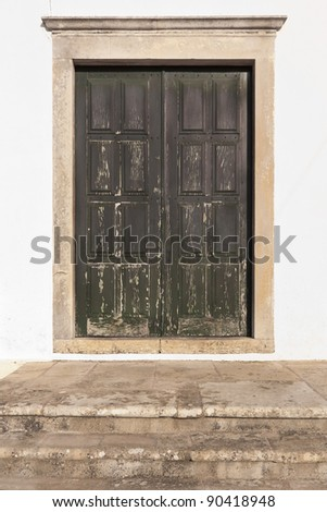 Old stained green double door with stone stairs - stock photo