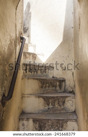 Old staircase leading to the light. - stock photo