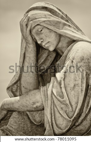 Old statue of a suffering woman with a vintage sepia look - stock photo