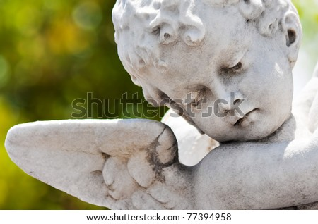 Old statue of an infant angel with a diffused green vegetation background - stock photo