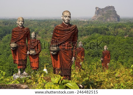 Old statues of Buddhist monks collecting alms dot the landscape surrounding the Win Sein Taw Ya Buddha in Kyauktalon Taung, near Mawlamyine, Myanmar.  - stock photo