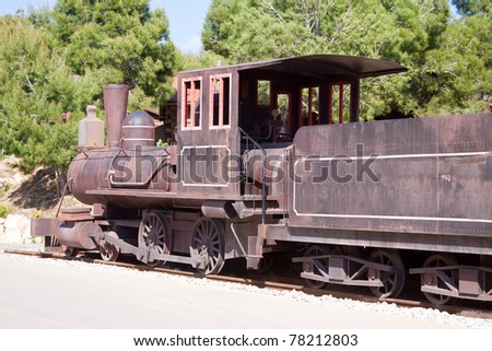 Old steam locomotive against pine trees - stock photo