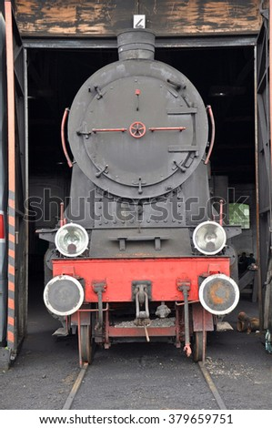 Old steam locomotive in depot for train - stock photo