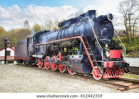 Old steam locomotive on rusty old rails and railway water tap