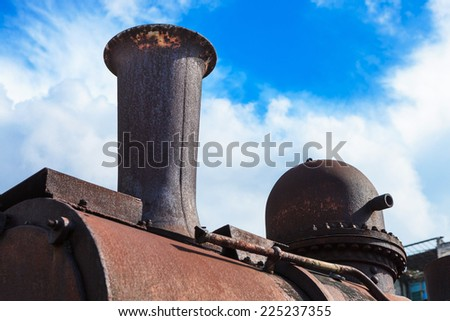 old steam locomotive pipe against the sky - stock photo