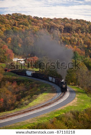 Old steam locomotive pulls freight through rural countryside in autumn - stock photo