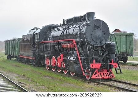 Old steam locomotive with carriage under heavy rain. Haapsalu, Estonia - stock photo