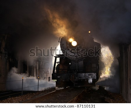 Old steam train pulling into a tunnel belching steam and smoke - stock photo