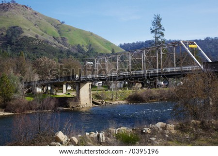 Old steel coloma bridge across river with green hill in background
