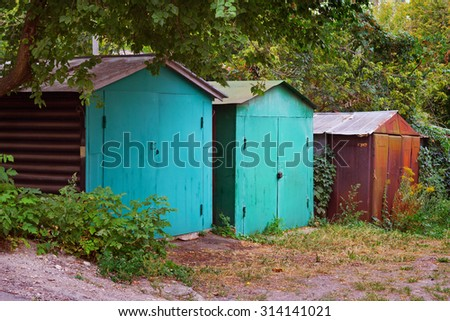 Old steel garages under the trees - stock photo