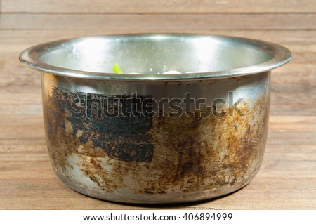 Old steel pot on wooden table. - stock photo