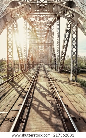 Old steel railway bridge on the river - stock photo