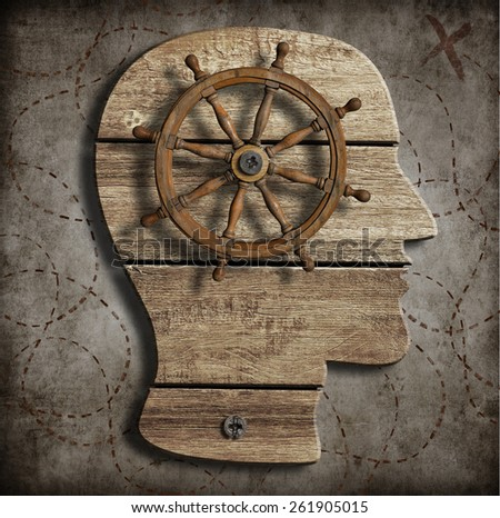 Old steering wheel over wood head silhouette as behavior control conception - stock photo