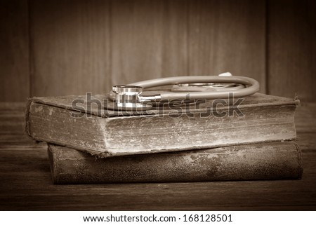 old Stethoscope on the old books,selective focus - stock photo