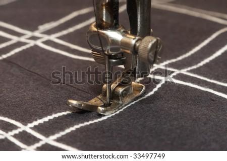 Old stitching machine stitch checked material - stock photo