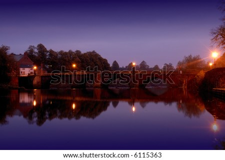 Old stone arch bridge crossing the River Dee in the Roman city of Chester  just before dawn