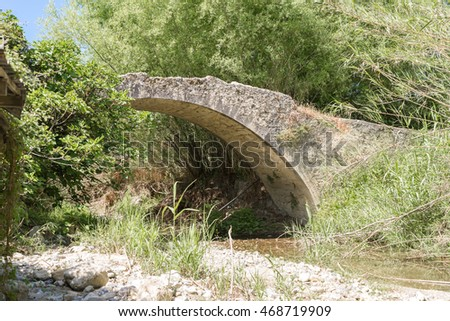 Old stone arch bridge on an old road in the southern foothills of the IDA range close to the mountain village Laloumas in south-central Crete, Greece