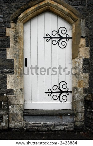 Old stone arched doorway with white wooden doors and black wrought iron accessories. - stock photo