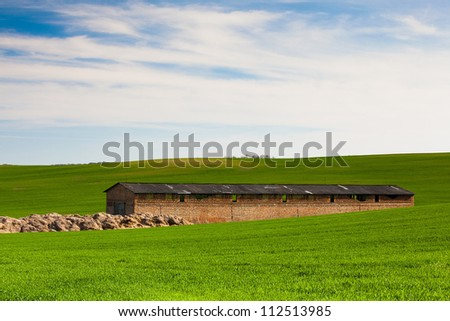 Old Stone Barn on the barley field in Moravia - stock photo