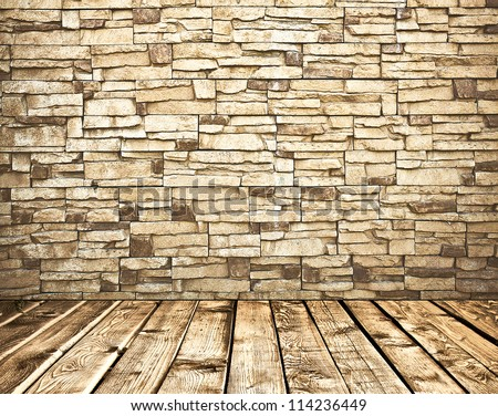 Old stone brick wall and tiled wooden floor inside grungy rural interior - stock photo