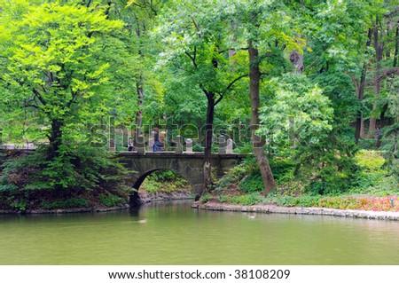 Old stone bridge across small stream in the woods. - stock photo