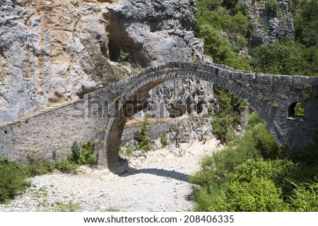 Old stone bridge of Kokkori or Noutsou at Epiros, Pindos mountains in Greece - stock photo
