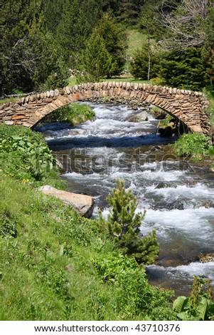 Old stone bridge over a mountain stream in Vall de Ransol (Pyrenees, Andorra) - stock photo